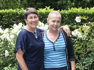 Two elderly females in rose garden